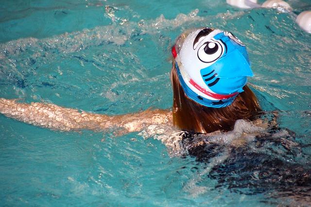 dívka v bazénu v koupací čepici